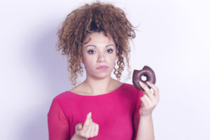 Funny woman eating donut feeling guilty.